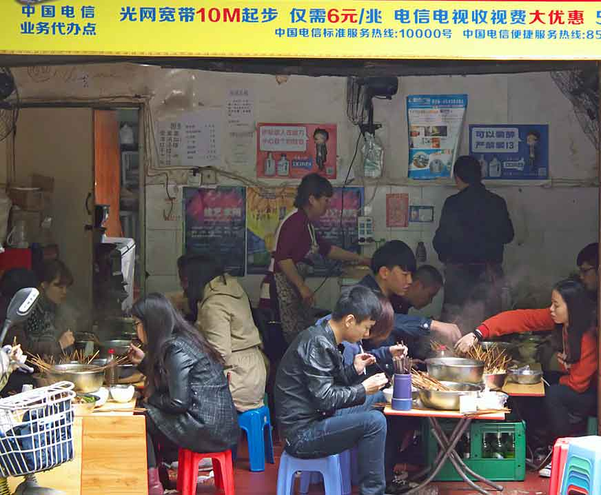 Students eating in one of the many small food stalls serving delicious Sichuan food that can be found along side streets in Chengdu, China. Photo: Anthony Hickey