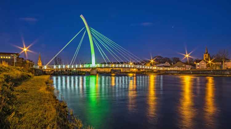 Ballina's Salmon Weir Bridge illuminated in green for St. Patrick's Day. It is flanked by St. Muredach's Cathedral (left) and St. Michael's Church (right). Above and to the left of St. Michael's Church, you can see the planet Jupiter, ascending in the east. Photo: Anthony Hickey