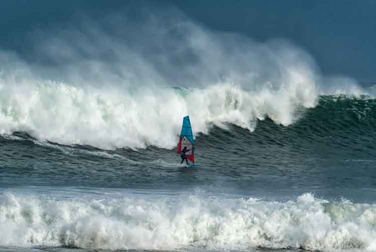 A windsurfer riding the enormous waves off Kilcummin, Co Mayo, during a winter storm. Photo Anthony Hickey